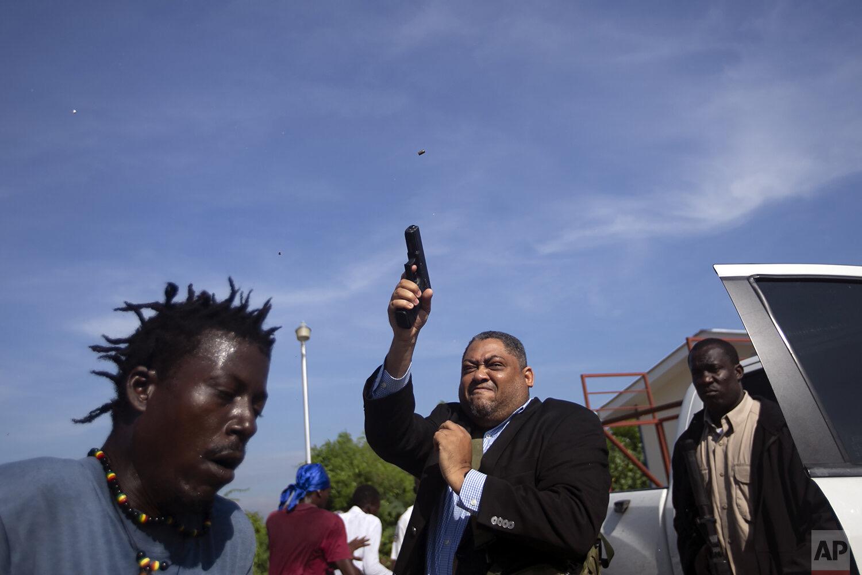 Le sénateur de l'opposition Ralph Fethiere tire son arme à l'extérieur du Parlement alors qu'il arrive pour une cérémonie de ratification de la nomination de Fritz William Michel au poste de Premier ministre à Port-au-Prince, Haïti, le 23 septembre 2019. Des membres de l'opposition ont affronté des sénateurs du parti au pouvoir, et Fethiere s'est retiré un pistolet lorsque les manifestants se sont précipités sur lui et des membres de son entourage. (AP Photo / Dieu Nalio Chery)