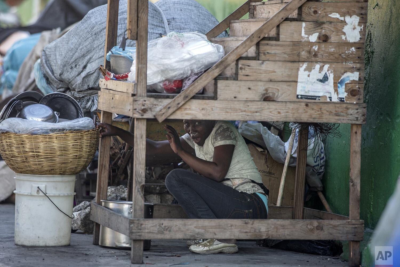 Une vendeuse de rue se cache lors d'affrontements entre des manifestants et des agents de la police nationale alors que les manifestants exigeaient la démission du président Jovenel Moïse | le 9 février 2019 | Photo : Dieu Nalio Chery / AP